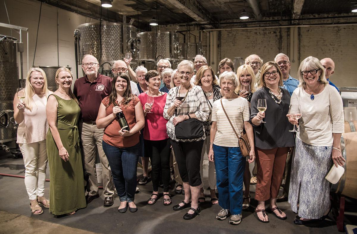 The volunteers who attended the celebration, with winery owner Kate MacDonald (holding the bottle of wine) and Ramona Toussaint, second from right, SPMH Tour Director.