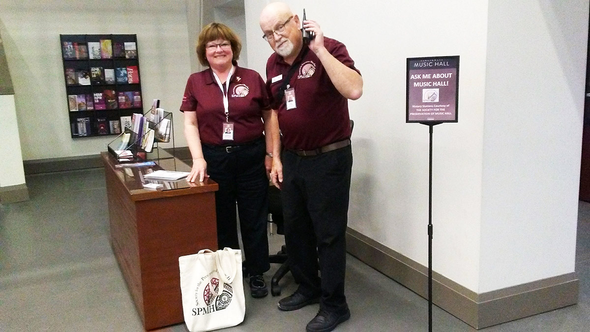 Volunteers Gayley Hautzenroeder and Dale Pepper at the Music Hall Information Desk