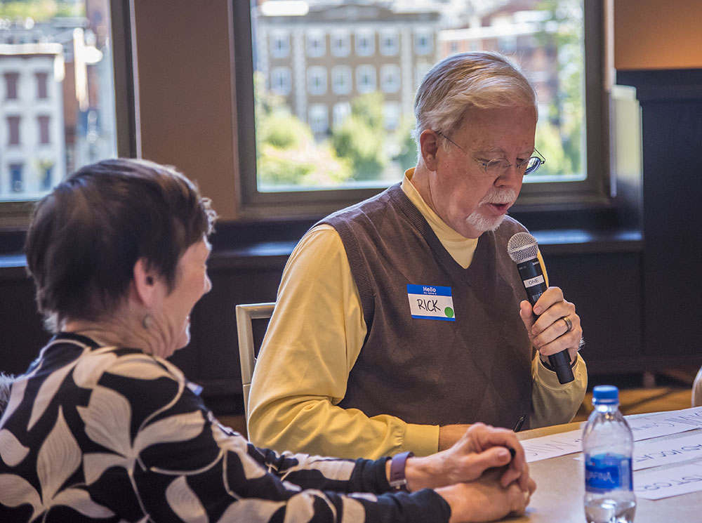 Board member Rick Pender relates his table's assessment as volunteer Sandra Geiser looks on