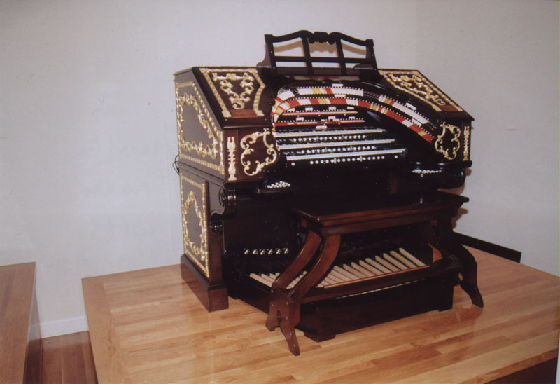 Wurlitzer Console on movable platform in display room – refinished Mahogany with gold leaf on ornamentation.