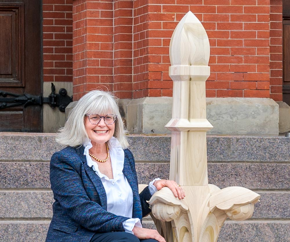 Thea Tjepkema on the steps of Cincinnati Music Hall with a model of a finial as designed by Samuel Hannaford