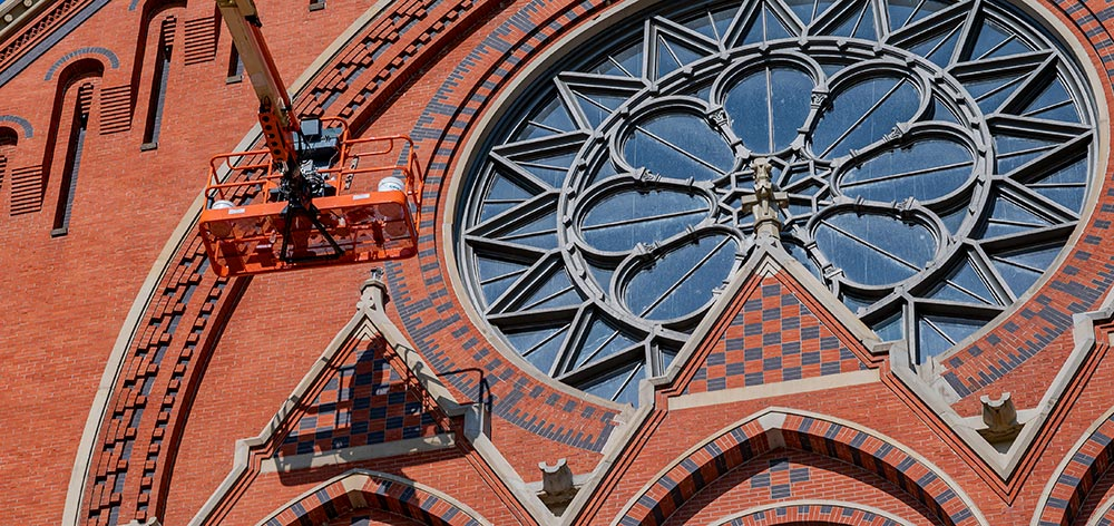 Cincinnati Music Hall showing the SSRG team and the boom bucket's shadow as they get close to replace the missing finial