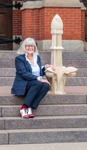 Historian/preservationist Thea Tjepkema on the steps of Cincinnati Music Hall with a model of a finial that is being restored.