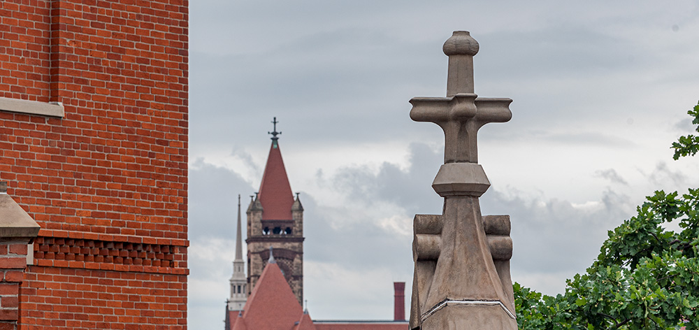 A restored finial on the west side of Cincinnati Music Hall, with the spires of City Hall and St. Peter in Chains Cathedral