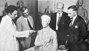 L->R: Sculptor Arturo Ivone presents the bust of Stephen Foster to Ernest Gwinner, Exposition Board; John J. Behle, Music Hall manager; and Cincinnati councilmember W. Meredith Yeatman